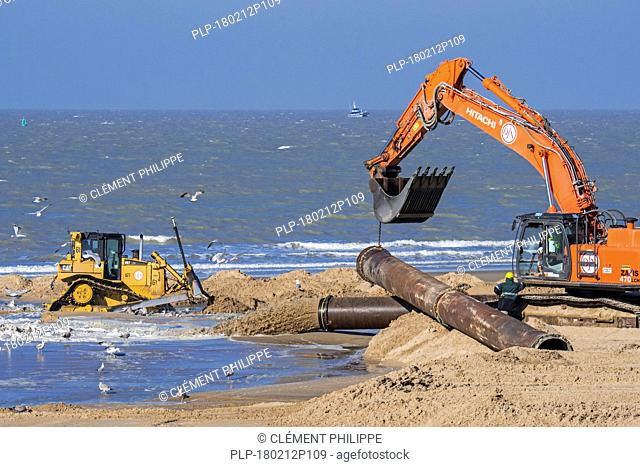 Bulldozer and hydraulic excavator installing pipeline during sand replenishment / beach nourishment works along the Belgian coast at Ostend, Belgium