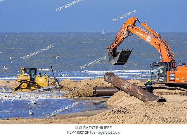 Bulldozer and hydraulic excavator installing pipeline during sand replenishment / beach nourishment works along the Belgian coast at Ostend, Belgium