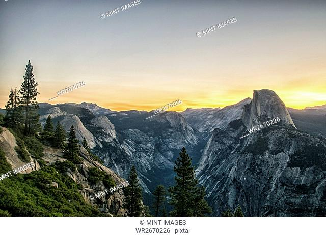 The mountain range in Yosemite valley at sunset, with distinct rock formations and snow covered slopes