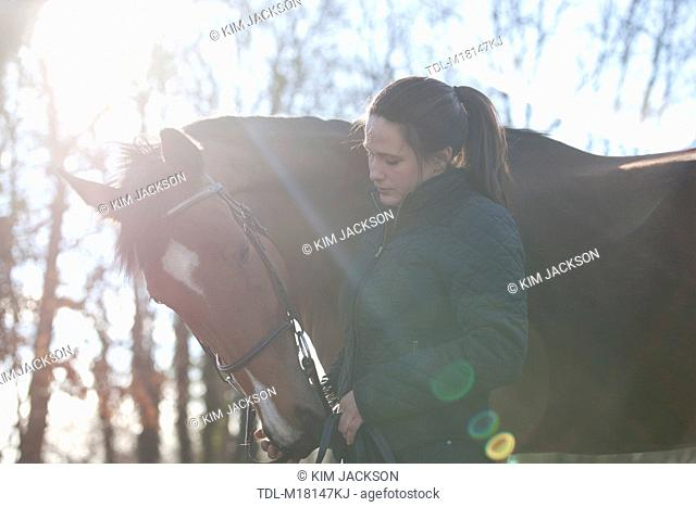 A young woman standing with a Thoroughbred horse