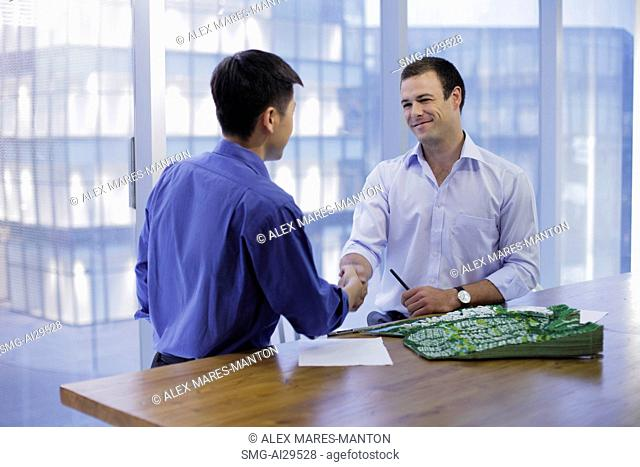 Young men shaking hands in modern office