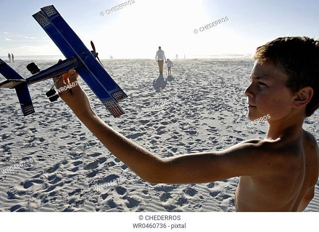 Side profile of a boy holding a model airplane