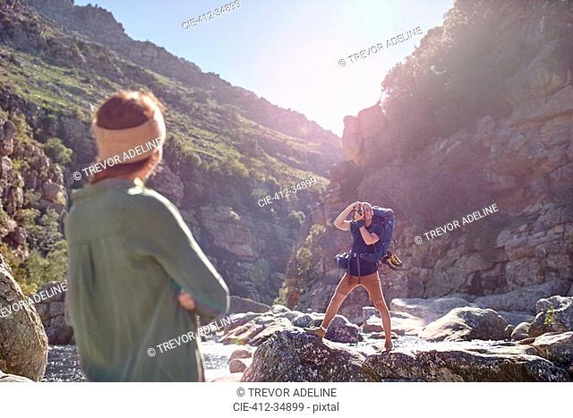 Young woman watching boyfriend hiking, photographing craggy cliffs