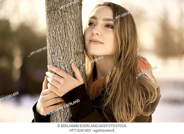 young woman leaning at tree in nature, winter season, in Cottbus, Brandenburg, Germany