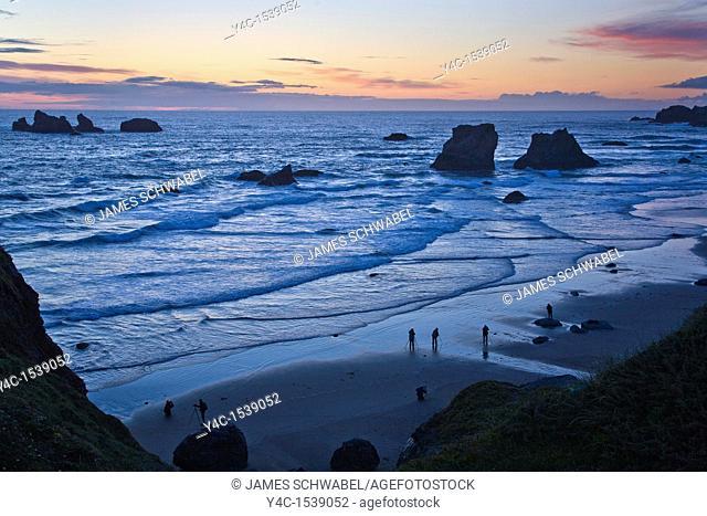 Photographers on Bandon Beach at sunset with seastacks on the Pacific Ocean coast of Bandon Oregon
