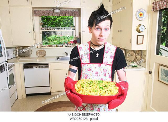 Man in kitchen holding a casserole
