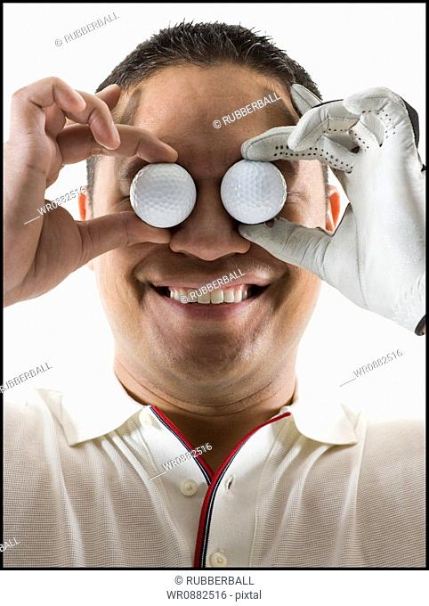Close-up of a mid adult man holding two golf balls in front of his eyes