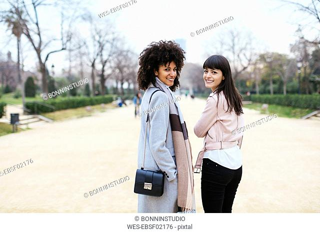 Spain, Barcelona, portrait of two smiling women in city park turning round