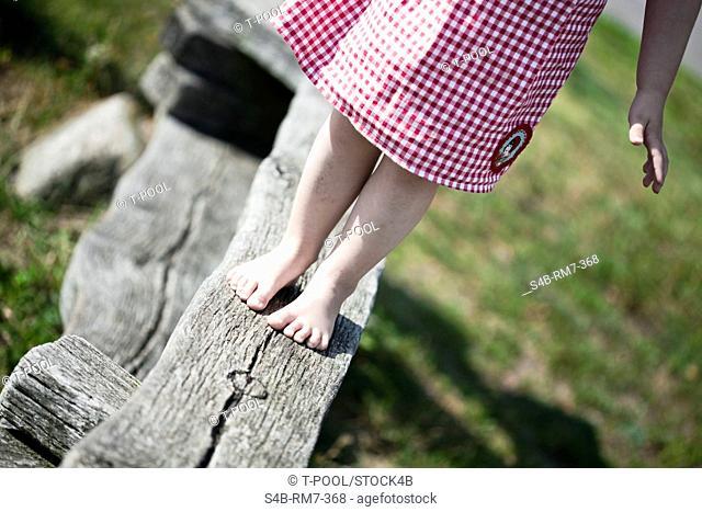 Girl balancing on wooden beam, Jesolo, Veneto, Italy