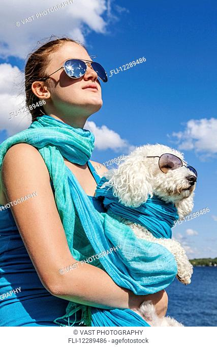 Girl and her dog wearing matching sunglasses; Balsam Lake, Ontario, Canada