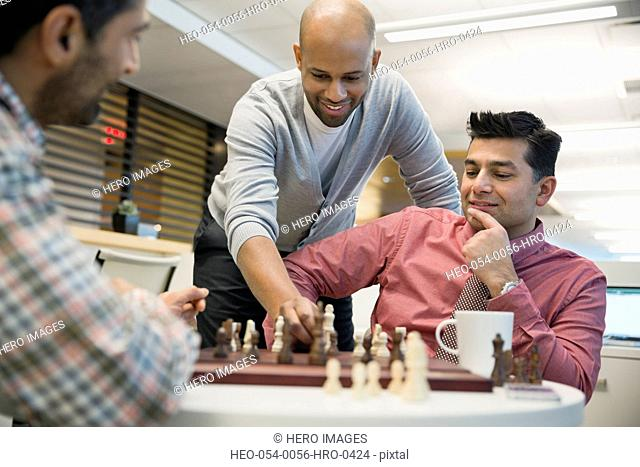 Businessmen playing chess at coffee table in office