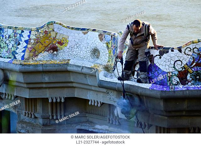 Man cleaning mosaics. Guell Park Parc Guell by Antoni Gaudi, Barcelona, Catalonia, Spain
