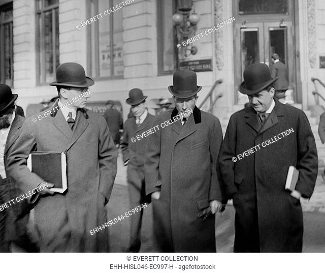 John D. Rockefeller and others walking from a New York Court House. He holds his head down, probably to avoid the photographer
