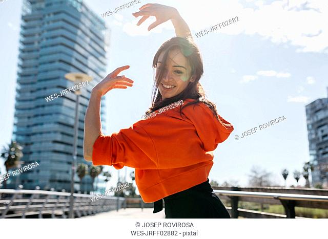 Young contemporary dancer wearing red hoodie shirt, practicing her passion
