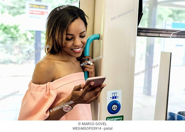 UK, London, smiling beautiful woman using cell phone on the train