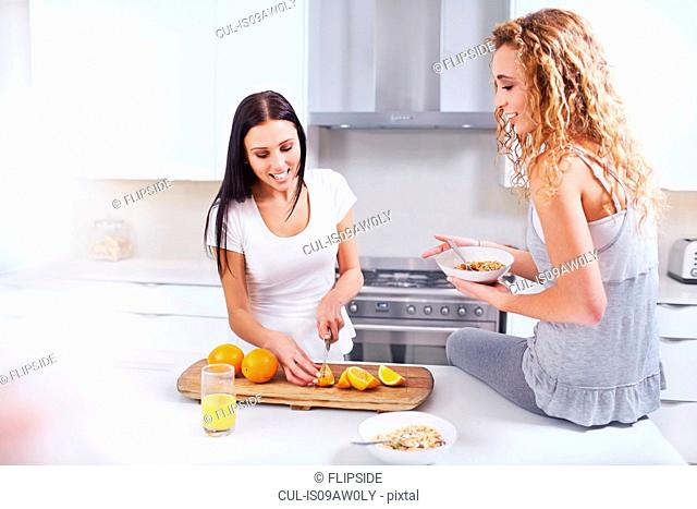 Two young female friends preparing breakfast oranges at kitchen counter