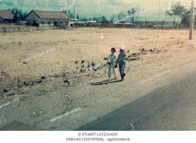 Two local Vietnamese people walk beside a road and an empty field ringed with barbed wire during the Vietnam War, 1968. ()