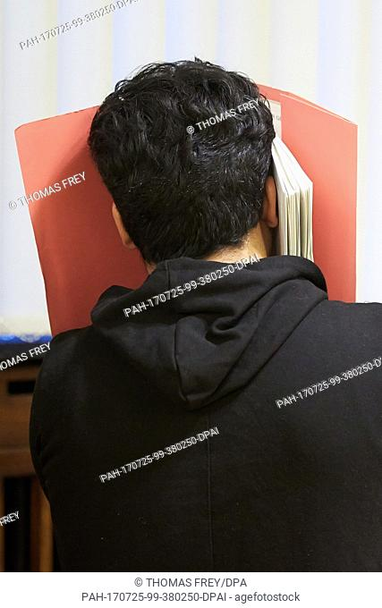 The defendant Khan A. hides his face at the Higher Regional Court in Koblenz, Germany, 25 July 2017. The federal prosecutor is accusing the 21 year old of...
