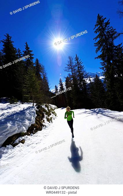A girl jogging at high altitude in snowy mountains