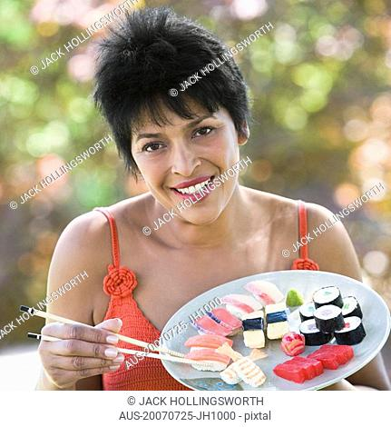 Portrait of a mature woman eating sushi with chopsticks