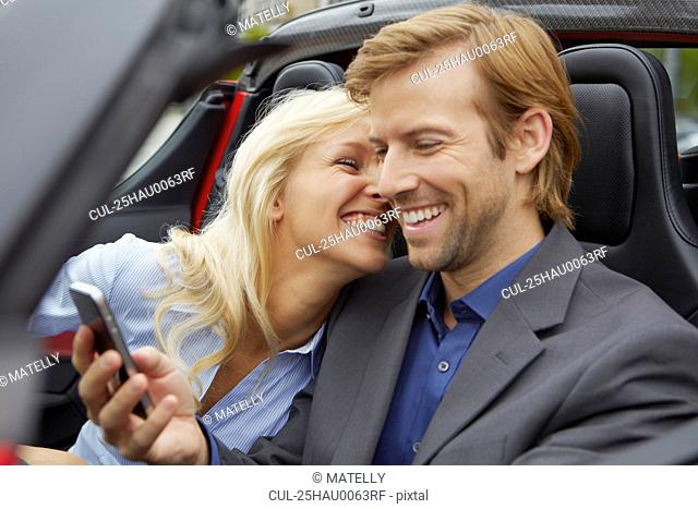 Couple in their electric sports car, fun
