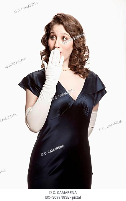 Woman in 1920's style dress covering mouth against white background