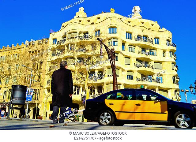 Rear view of a man and a taxi in front of La Pedrera or Casa Mila. Designed by catalan architect Antoni Gaudi and listed as World Heritage by UNESCO