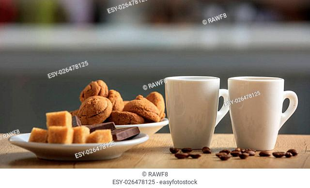 Cups of coffee and cookies on an office table