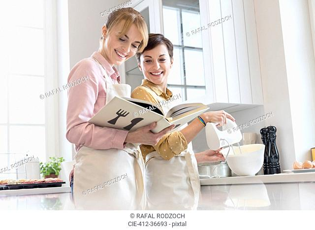 Female caterers with cookbook baking in kitchen, using electric hand mixer