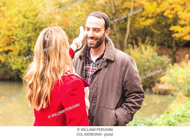 Mid adult couple in park, standing face to face, woman touching man's face