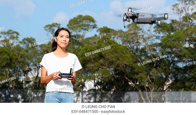 Woman control fly drone with at outdoor