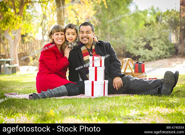 Young mixed-race family enjoying christmas gifts in the park together