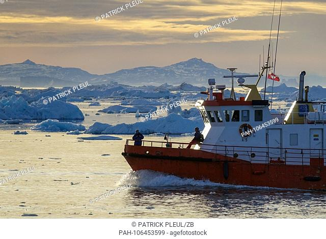 27.06.2018, Gronland, Denmark: A ship cruises late evening between icebergs over the water in front of the coastal town of Ilulissat in western Greenland