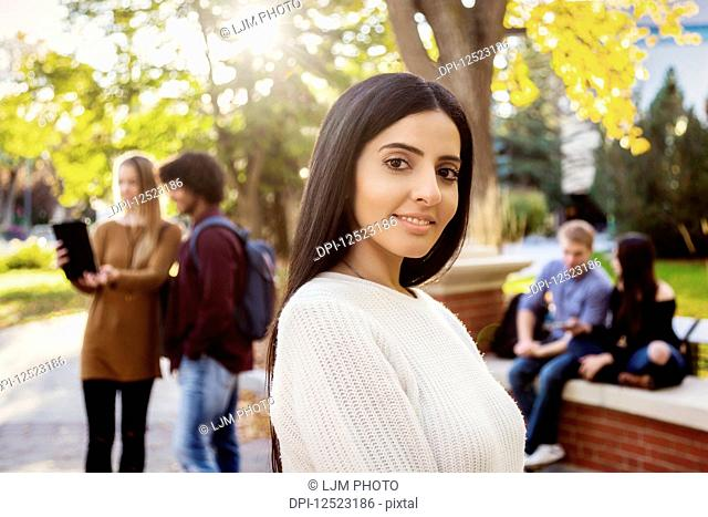 A young female university student of Lebanese ethnicity poses while her friends talking are together in the background on the university campus; Edmonton