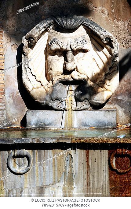 Italy. Lacio. Rome. Fountain of arge mask at Piazza di Pietro di Iliria. The mask and bathtub come from ancient Roman Thermae. UNESCO World Heritage