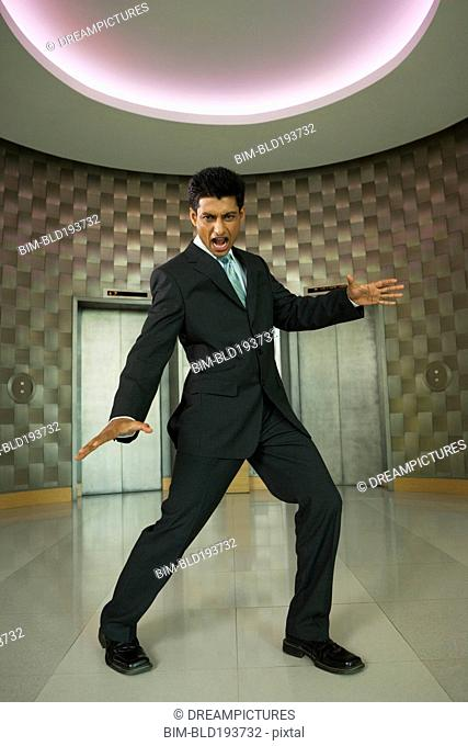 Playful Indian businessman in office lobby