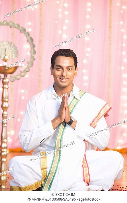 Man praying in traditional South Indian dress