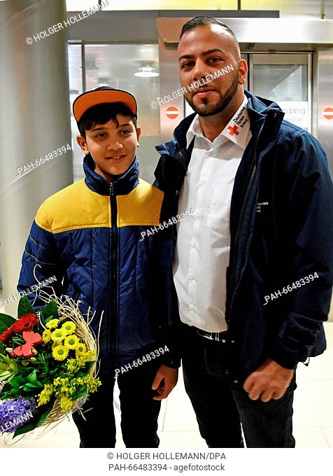 Afghan refugee boy Mahdi Rabani stands with Rani Hijazi, refugee advisor with the German Red Cross district chapter, in the arrivals hall of the...