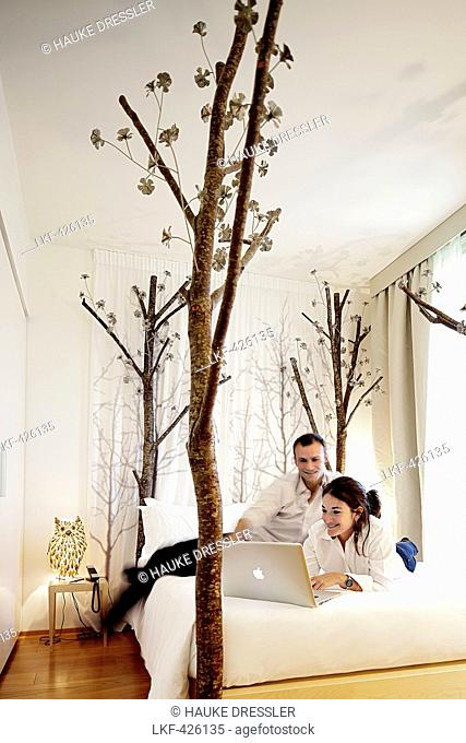 Young couple with laptop on a hotel bed, Milan, Lombardy, Italy