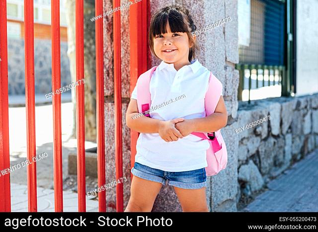 Brunette girl carrying a pink backpack at the entrance door of the school. School concept