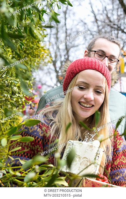 Young couple with gifts and mistletoe twigs