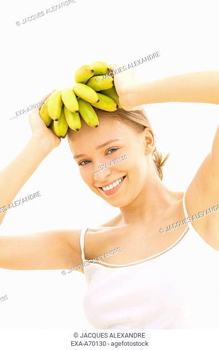 woman helds bananas on head