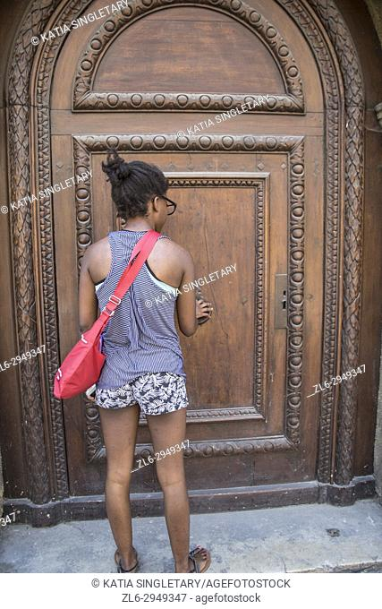 African American Teenager about to enter in a building with a huge brown wood door in France