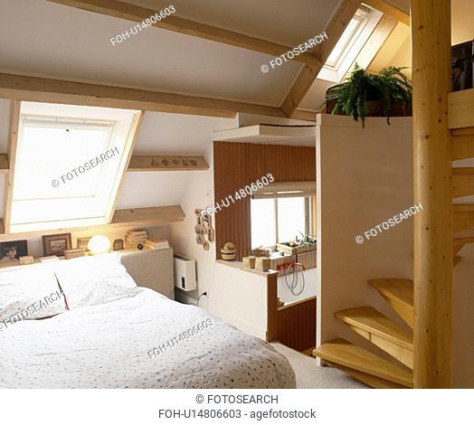 Divan bed below Velux window in attic conversion bedroom with pine staircase