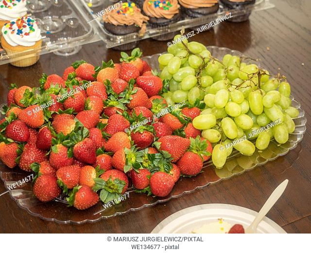 Grapes and strawberries in a large bowl on party table