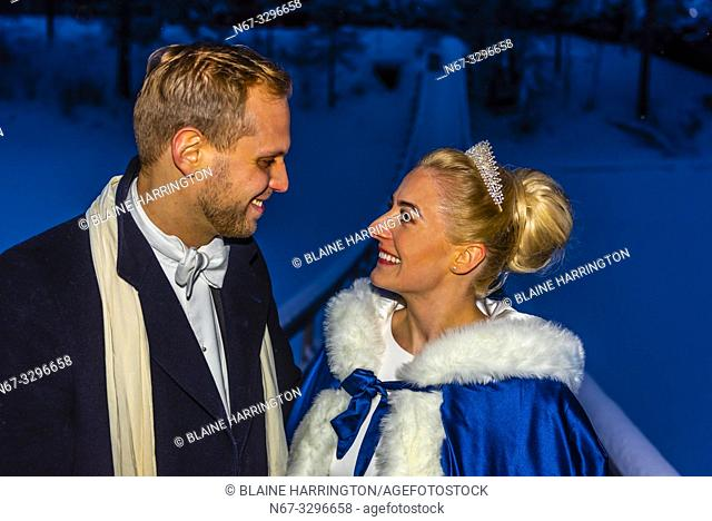 A Newlywed Norwegian couple pose for a photo on a cold winter evening after their wedding, Trysil, Norway