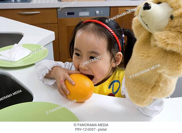 a girl in the kitchen eating orange