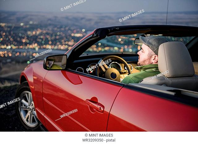 A Caucasian male parked in his convertible sports car watching the sunset over the Clearwater River and the city of Lewiston Idaho