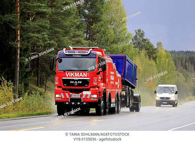 Salo, Finland. September 28, 2018: Gravel transport trailer being towed by MAN heavy duty tow truck of Hinauspalvelu Vikman along highway on a rainy day