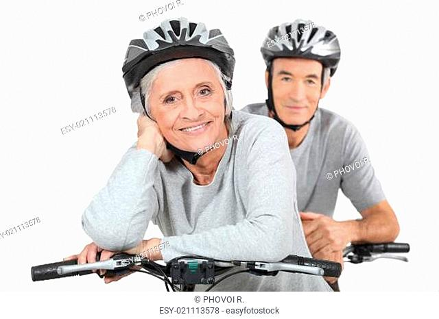 An elderly couple riding their bikes together